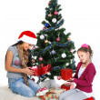 Mother and daughter near a christmas tree with gifts, isolated on a white b - Stock Photo