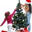 Mother and daughter near a christmas tree with gifts, isolated on a white b — Stock Photo #7828486