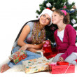 Mother and daughter near a christmas tree with gifts, isolated on a white b — Stock Photo #7828498