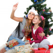 Stock Photo: Mother and daughter near a christmas tree with gifts, isolated on a white b