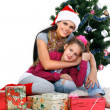Mother and daughter near a christmas tree with gifts, isolated on a white b — Stock Photo #7828520