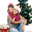 Mother and daughter near a christmas tree with gifts, isolated on a white b — Stock Photo #7828523
