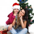 Mother and daughter near a christmas tree with gifts, isolated on a white b — Stock Photo #7828527