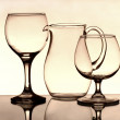 Two wineglasses and a jug on the mirror — Stock Photo