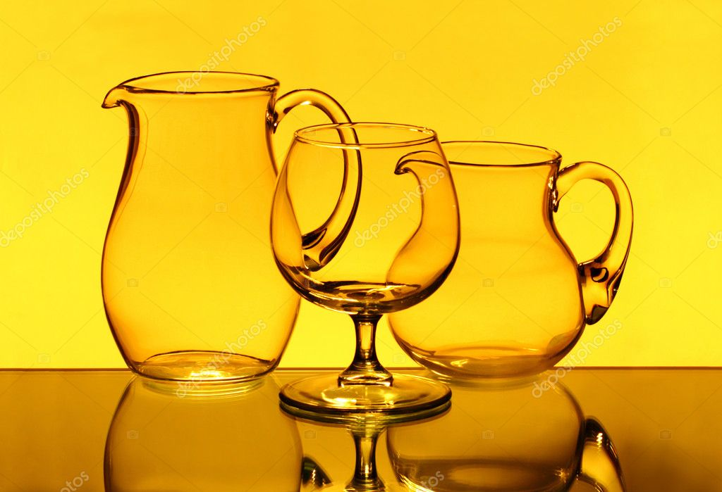 Two empty jugs and one wineglass in the yellow light  Stock Photo #6856714