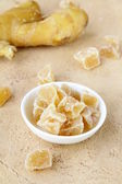 Candied ginger and fresh ginger on a beige background — Stock Photo
