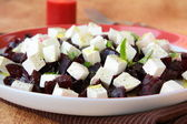 Appetizer salad of beets and goat cheese with basil and olive oil — Stock Photo