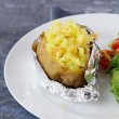 Baked potato filled with sour cream and cheese, with salad — Stock Photo