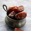 Dates in cup on grey background — Stock Photo