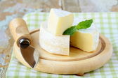 Cheese camembert on a wooden plate and herbs — Stock Photo