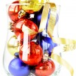 Glass filled with colorful holiday ornaments and christmas decoration over — Stock Photo #7618374