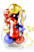 Glass filled with colorful holiday ornaments and christmas decoration over — Stock Photo