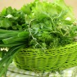 Fresh green grass parsley dill onion herbs mix in a wicker basket — Stock Photo #7883880