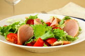 Salad with tomato and salami on plate — Stock Photo