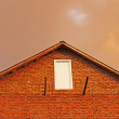 Stockfoto: Fragment of brick house in background reddish thunderclouds.