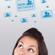 Young girl looking at social type of icons and signs - Stock Photo