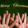 Merry christmas happy finger group with smiley faces on green ba - Stock Photo