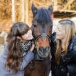 Two girls holding a horse — Stock Photo