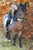 Young girl on horseback stroking a horse — Stock Photo