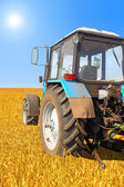 Tractor in a field, agricultural scene in summer — Stock Photo