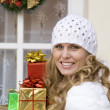 Woman arriving at christmas party laden with gifts. — Stockfoto