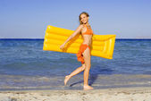Happy young woman walking on beach with airbed on summer vacation — Stock Photo
