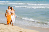 Young women walking along seashore on beach summer vacation or spring break — Stock Photo