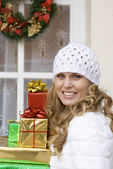 Woman arriving at christmas party laden with gifts. — Foto de Stock