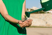 Conservation concept, child holding plant while watering it — Stock Photo
