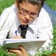 Student writing or studying outdoors on campus — Stock Photo #6950040