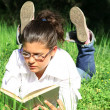 Girl laying on grass reading book outdoors in summer on campus — Stock Photo #6950043