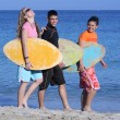 Young surfers walking along beach happy and smiling — Stock Photo