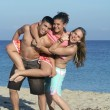 Smiling group of youth, kids,or teenagers playing, piggyback on beach summe — Stock Photo