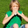 Child with hayfever allergy sneezing into tissue - Stock Photo