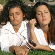Teens students relaxing on campus listening to music sharing earphones and — Foto Stock