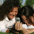 Stock Photo: Students on campus with mobile or cell phone laughing and having fun