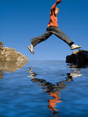 Fit healthy active kid jumping rocks on vacation — Stock Photo