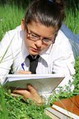 Student writing or studying outdoors on campus — Stock Photo