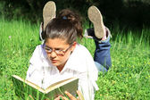 Girl laying on grass reading book outdoors in summer on campus — Stock Photo