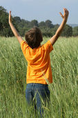 Happy summer child arms raised to the sky and sun — Stock Photo