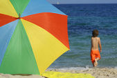 Beach summer vacation on holiday with colourful sunshade — Stock Photo