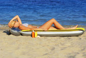 Woman laying on lilo airbed on beach sunbathing with tanning lotions — Stock Photo