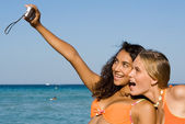 Young taking photos with camera at beach — Stock Photo