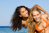 Diverse teens playing at piggyback on summer holiday or spring break vacati — Stock Photo