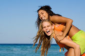 Diversity, mixed race friends playing piggyback on summer holiday at beach — Stock Photo