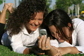 Students on campus with mobile or cell phone laughing and having fun — Stock Photo