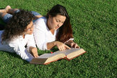 Young women reading at bible camp or study group — Stock Photo