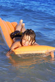 Young kid floating in sea playing on airbed or lilo — Stock Photo