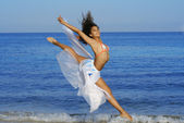 Happy healthy woman leaping on seashore on summer vacation — Stock Photo