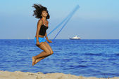 Healthy woman skipping on beach on summer vacation — Stock Photo